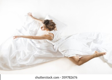 Ballet dancer rehearsing in her sleep dressed in white with white sheets, on white background. Expressive woman in action, dreaming concept. Dreaming of becoming professional dancer.