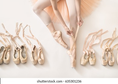 Ballet dancer sits on the white floor and dresses a beige pointe shoe in the studio. She wears a light dance wear and a peach tutu. On the sides there are ballet shoes. Top view photo.