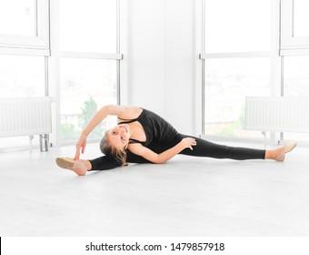 Ballet dancer teen girl is making morning stretch in completely white dance studio