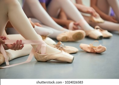 Ballet dancer tying ballet shoes. Close up ballet girl putting on her pointe shoes sitting on the floor, blurred background.