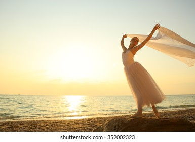 ballet dancer with a veil at sunset on the coast