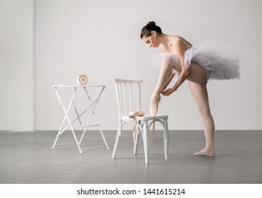 ballet dancer in a white dress with chair tying her ballet slippers, for wall background.