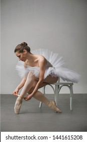 ballet dancer in a white dress sitting on a chair and tying her ballet slippers, for wall background.