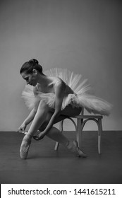 ballet dancer in a white dress sitting on a chair and tying her ballet slippers, for wall background black white.