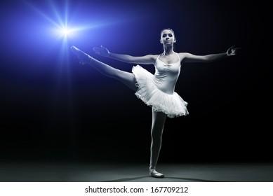 Ballet dancer in white tutu posing on one leg