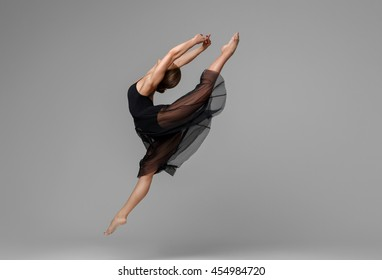 Ballet dancer woman black dress on gray background