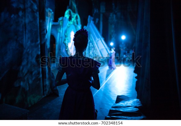 ballet, dancing, magic concept. in ghostly blue light decoration for perfomance and tender silhouette of slender ballerina wearing pink dress with short sleeves waiting for her turn backstage