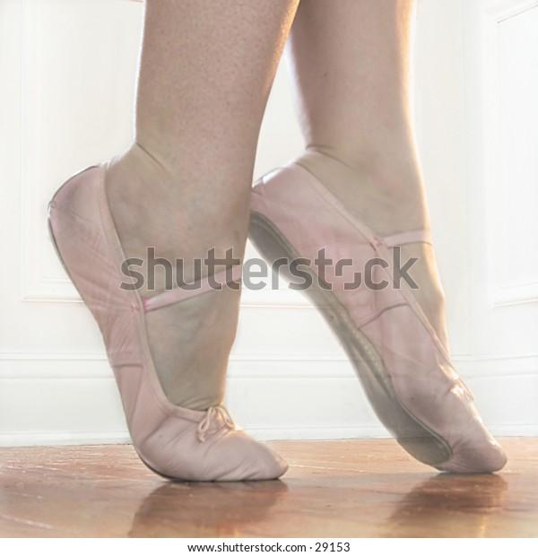 Ballet feet in Releve on a hardwood dance floor