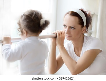 Ballet instructor directs little cute ballerina during dance practice. Shallow depth of field. Focus on woman