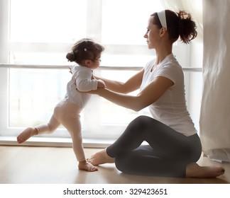 Ballet instructor directs little cute ballerina during dance practice