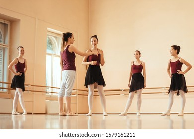 ballet instructor holding a class to group of ballerinas and communicating with them at dance studio.