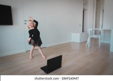 Ballet lesson online. Little girl dancing while looking at computer at home.