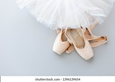 Ballet pointe shoes and white tutu skirt on gray background. Concept of dance, spring, ballet school, ballerinas clothes, stuff and things. Top view, flat lay. Copy space.