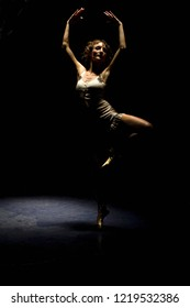 Ballet pose in a passé. Dancer is in pointe shoes and has long curly hair. Shot is in low key with a spot light