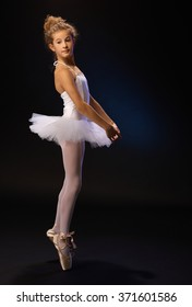 Ballet student exercising in ballet costume, standing on her toes.