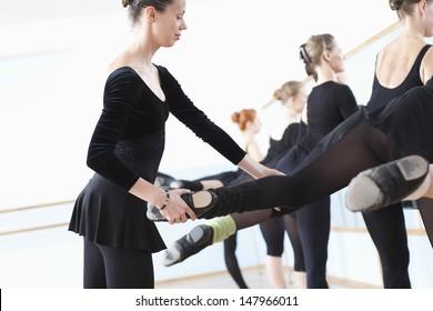 Ballet teacher adjusting foot positions of ballerinas at the barre