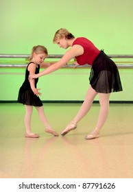 A Ballet Teacher Helps a Girl Dance Student with her lesson