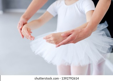 Ballet teacher helps little ballerina in classical dance school. Female dance trainer is teaching kid girl to do choreographic position with hands. Practicing for children. Close up.