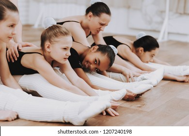 Ballet Training of Girls on Floor with Teacher. Classical Ballet. Girl in Balerina Tutu. Training Indoor. Cute Dancers. Performance on Wooden Floor. Dancing Practice. Girls in White Dresses.