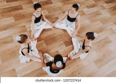 Ballet Training of Group of Young Girls on Floor. Classical Ballet. Girl in Balerina Tutu. Training Indoor. Cute Dancers. Performance on Wooden Floor. Dancing Practice. Girls in White Dresses.