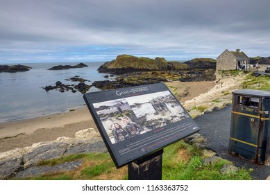 Ballintoy, UK - August 6, 2018 : Visitor information sign with Ballintoy harbor in the background, Northern coast of County Antrim, which was used as a filming location in Game of Thrones TS series.