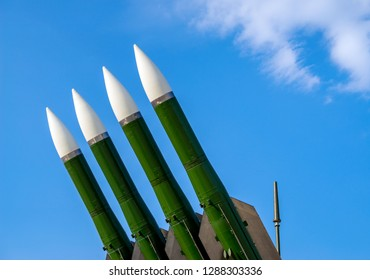 Ballistic missile launcher with four cruise missiles on powerful mobile transportation on background blue sky, antiaircraft forces, military industry