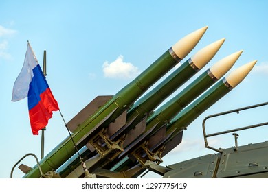 Ballistic missile launcher with four cruise missiles on powerful mobile transportation on background blue sky, antiaircraft forces, military industry. Flag of Russia