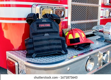 Ballistic vest and red firefighter helmet on fire truck bumper. Concept of evolving role of fire department response to mass casualty shooting and terrorism