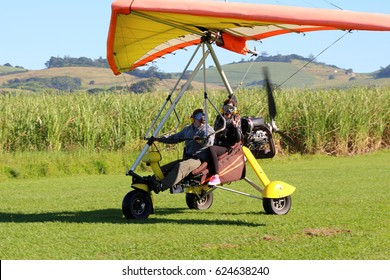 BALLITO, SOUTH AFRICA - 7 APRIL 2017: A man & woman prepare to take off in a microlight. In affluent countries, microlights account for a significant percentage of civilian-owned aircraft. Editorial.