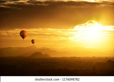 Balloon floating in the clouds at sunset.