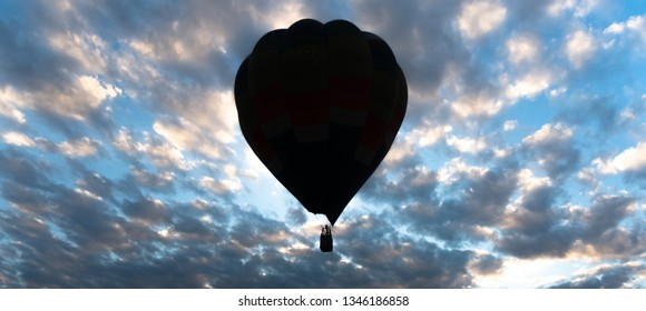 The balloon floats in the sky amidst the clouds in the evening while the sun is hiding.