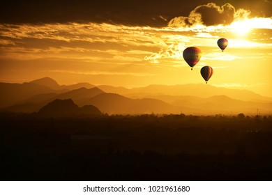 The balloon floats in the valley at sunset.