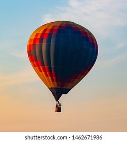 Balloon flying in the sky in the rays of the sunset.