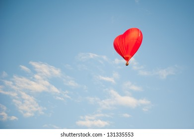 Balloon in the form of heart in the sky with clouds