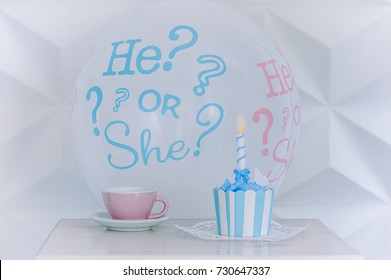 """A balloon """"he or she"""" from a gender reveal party with sweet cake and cup of tea."""