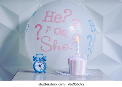 """A balloon """"he or she"""" from a gender reveal party with sweet cake and alarm clock."""