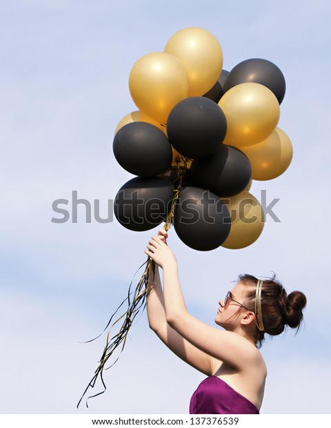 Balloons!  Attractive teen hanging on to a bunch of helium filled balloons.