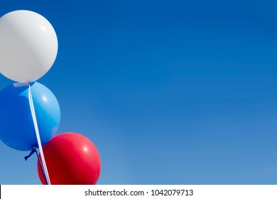 Balloons of colors of the Russian national flag against the blue sky. The concept of national Russian holidays: June 12, independence day of Russia and November 4, national unity day. Copy space