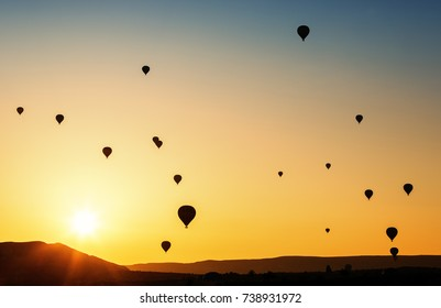 Balloons flying in the sky at sunrise.