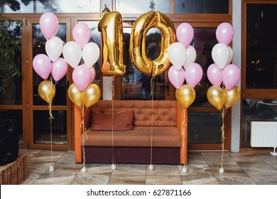 Balloons in form of number 10 hang before the couch