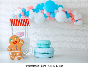 balloons ice cream cart on festive white brick background with big gingerbread man. Bright blue pink background with free space giant macaroons Event children's party space text sweets, holiday treats