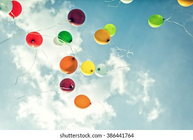 Balloons on cloudy sky