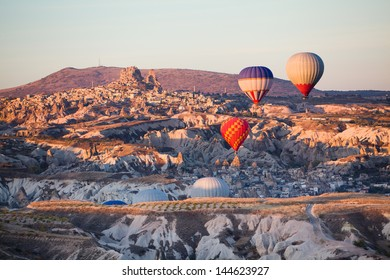 Balloons over Uchisar castle in Cappadocia at sunrise, Turkey
