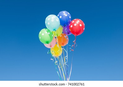 balloons in polka dots against the blue sky