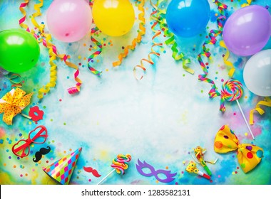 Balloons, present or gift box, confetti, candy, bow tie, sunglasses and streamers on colorful background with copy space. Top view. Birthday, carnival or party background