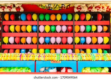 balloons and prizes at a dart throwing game booth at a carnival, fair, or amusement park in America