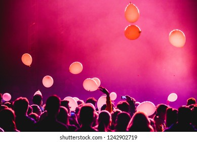 Balloons, red light, crowd at concert