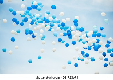 Balloons in white and two shades of blue on a cloudy sky background.