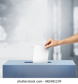 Ballot box with hand person vote on blank voting slip at outdoor background