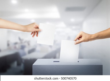 Ballot box with two hand person vote on blank voting slip at offic. voting concept.